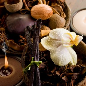photo of vanilla beans with a white flower and brown candles