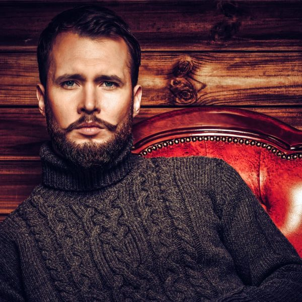 photo of a man sitting in a cable knit brown sweater in a red leather chair