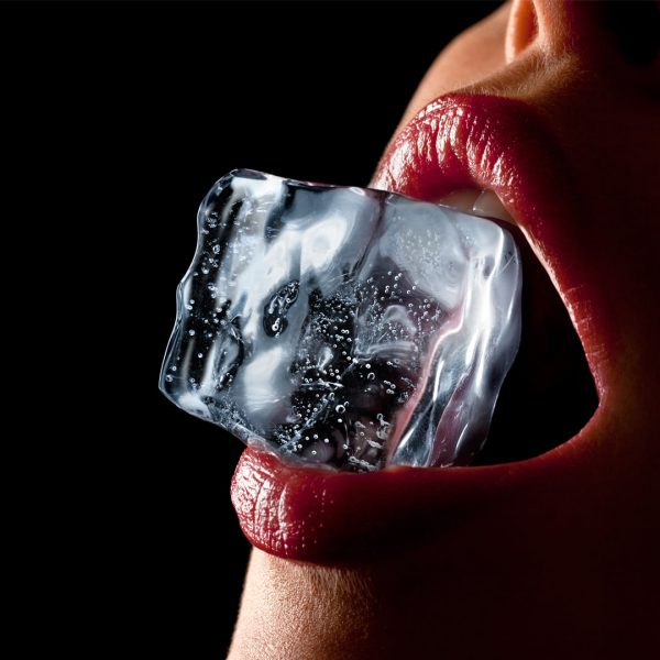 photo of woman holding a piece of ice in her teeth