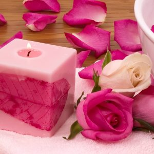 Pink candle with rose petals on a pink towel