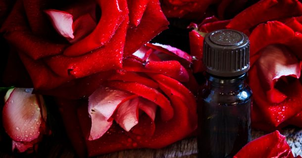 Brown fragrance oil with red roses on wood