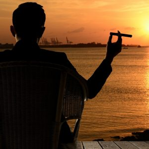 photo of a man sitting in a chair overlooking a sunset and smoking a cigar
