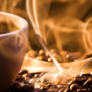 photo of a steaming cup of coffee and whips of smoke with coffee beans