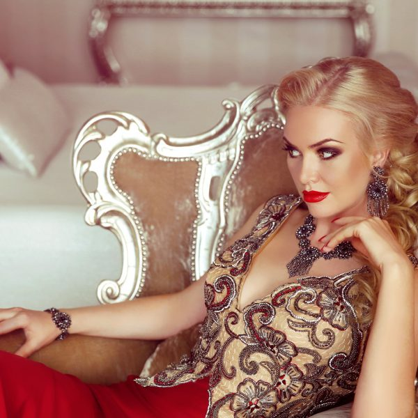 photo of a blonde woman sitting in a beautiful gold and red dress next to a white bed