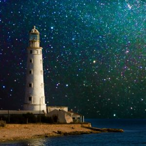 photo of a white lighthouse with a starry night in the background