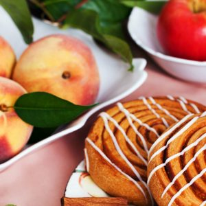 photo of cinnamon rolls with peaches in a white dish