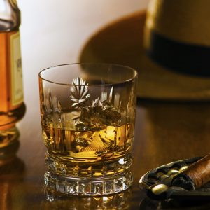 photo of a glass of cognac with hat in the background and cigar next to it
