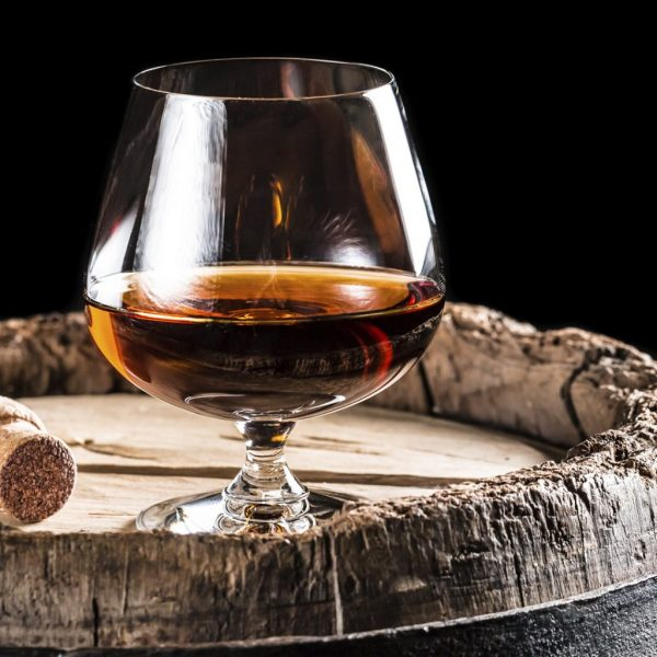 photo of a glass sitting on an oak barrel with cork