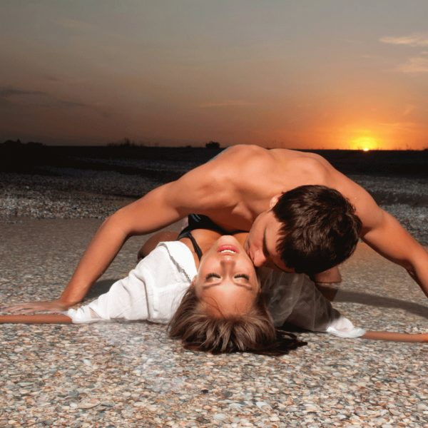 photo of a man and woman embracing on a beach during sunset
