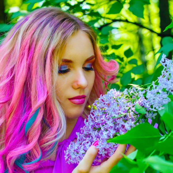 photo of a woman with pink and blue coloured hair smelling purple lilac flowers