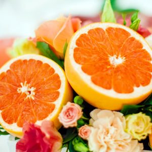 photo of cut oranges within a bed of small roses