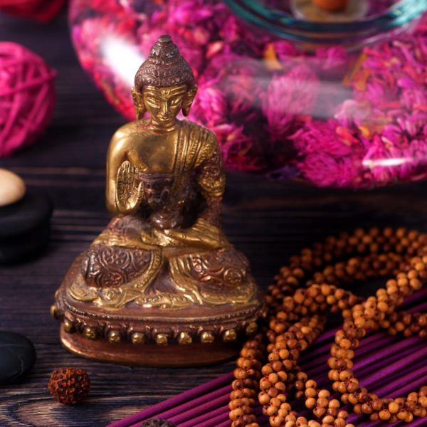 photo of a Tibetan statue and incense