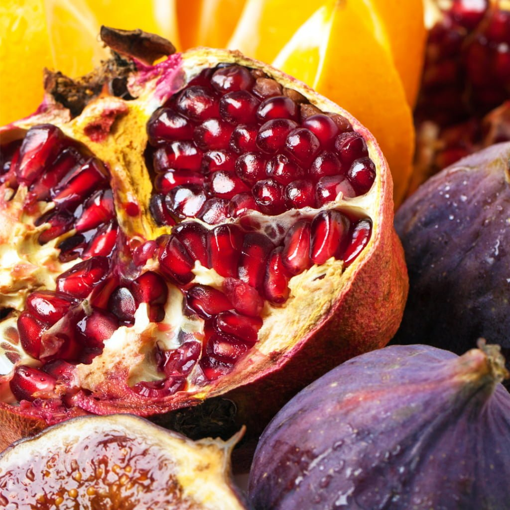 photo of a pomegranate and oranges with figs