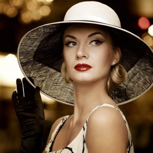 photo of a woman in a white hat, well dressed and wearing gloves