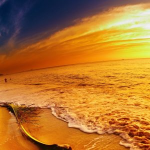 photo of an orange sunset on the beach with the waves coming in