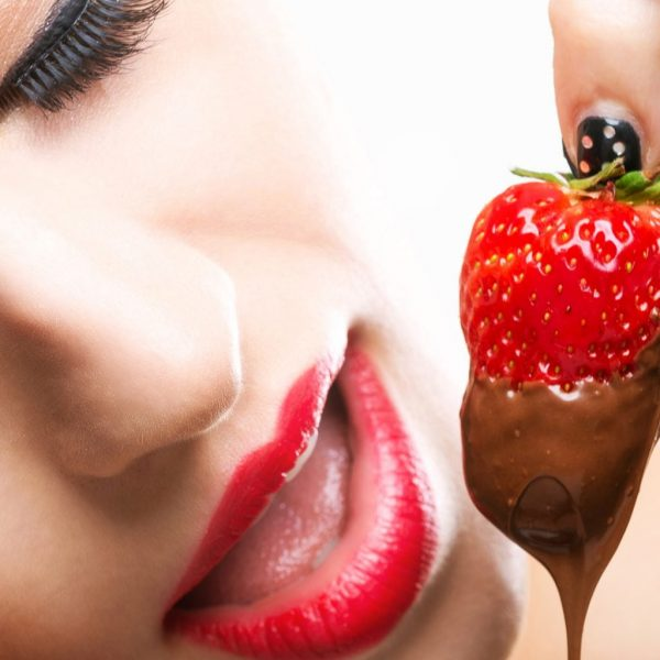 photo of woman about to eat a chocolate covered strawberry