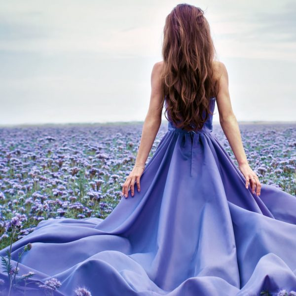 photo of a woman in a flowing purple dress standing in a field of lilac